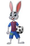 Footballeur de lapin avec une boule dans l'uniforme bleu et rouge Illustration Stock