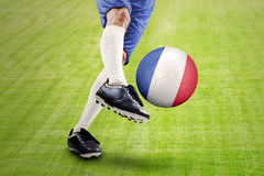 Footballeur donnant un coup de pied une boule le champ Photographie stock libre de droits