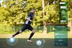 Footballeur jouant avec la boule sur le terrain de football Photos stock