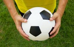 Footballeur tenant un football photographie stock libre de droits