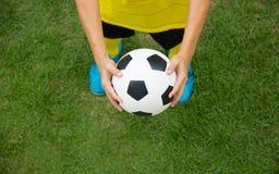 Footballeur tenant un football photographie stock