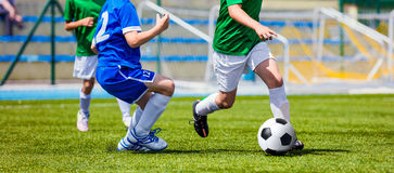 Footballeurs d'enfants fonctionnant avec la boule Enfants dans des chemises bleues et vertes Image libre de droits