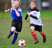 Footballeurs de la jeunesse fonctionnant après la bille Photo libre de droits