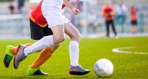 Footballeurs fonctionnant après la boule sur le lancement Match de football photographie stock libre de droits