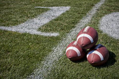 Footballs on a playing field Stock Image