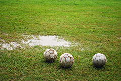 Footballs on a Wet Field Royalty Free Stock Image