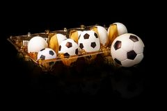 Footballs among the white eggs in the egg tray. Soccer bolls in the egg tray. So there appear soccer balls. Footballs among the white eggs in the egg tray Royalty Free Stock Photos
