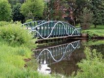 Footbridge отражая в пруде Стоковая Фотография