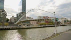 Footbridge соединяя 2 банка реки, осмотренного от банка против городского пейзажа видеоматериал