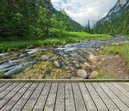 Footbridge across the mountain stream Royalty Free Stock Photography