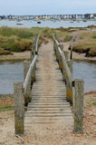 Footbridge across stream with row of beach huts in distance Stock Photography