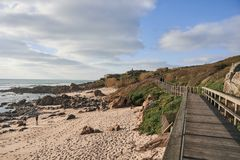 Footbridge along the beach rises to the top of the cliff royalty free stock photography