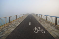 Footbridge With Bicycle Sign In The Fog Stock Photo