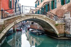 Footbridge and boats in water canal, Venice - Italy Royalty Free Stock Photos