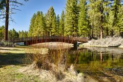 Foot Bridge over Spring Creek. A footbridge crosses Spring Creek, at Collier Memorial State Park off of Highway 97 near Chiloquin Oregon. It`s crystal-clear, ice stock photos