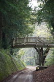 Footbridge in the English countryside. Over a narrow road Stock Image