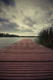 Footbridge and lake. The picture shows a lake and a cloudy sky Royalty Free Stock Images
