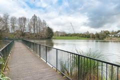 A footbridge on a lake surrounded by lush greenery royalty free stock photo