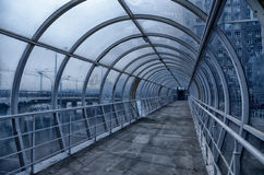 Footbridge made of metal and glass for people on a busy road overpass for pedestrians. inside view stock photography