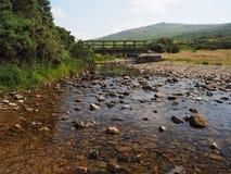Footbridge nad rzeki Lyd z kryształem - jasna woda i skały, Dartmoor Obraz Stock
