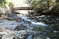 Footbridge Over Creek With Trees And Rocks Royalty Free Stock Image