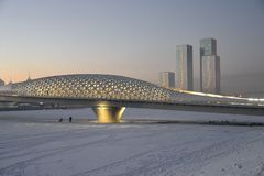 Footbridge over the Ishim river in Astana. Astana in December. Illuminated by electric light pedestrian bridge over the Ishim river in Astana at sunset. In the stock photo