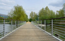 A footbridge over a lake in the middle of a business park Stock Photos