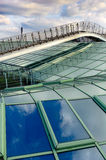 Footbridge over modern glass roof. With blue sky and clouds royalty free stock photo