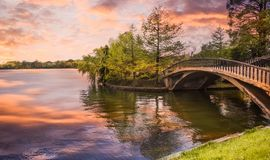 Footbridge over the pond in the city park at sunset. Styled stock photo with wooden bridge in twilight atmosphere in Herastrau royalty free stock images