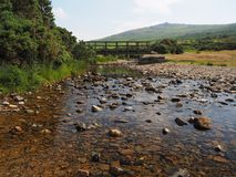 Footbridge over the River Lyd with crystal clear water and rocks, Dartmoor stock image