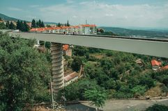 Footbridge over valley with apartment building and trees. Footbridge over valley with apartment building in the midst of trees and hilly landscape at Covilha stock photo