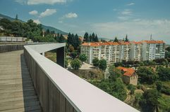 Footbridge over valley with apartment building and trees. Footbridge over valley with apartment building in the midst of trees and hilly landscape at Covilha royalty free stock image