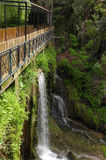 Footbridge over a waterfall. Stock Images