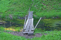 The footbridge. The photograph depicts a carelessly made, devastated wooden footbridge. It is made of rough boards. It is flush over the standing, covered royalty free stock image