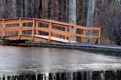 The footbridge at the pond. An icy pond by the footbridge on a cold day Stock Photos