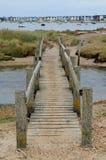 Footbridge przez strumienia z rzędem plażowe budy w odległości Fotografia Stock