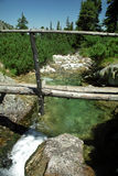 Footbridge and smarald water. Small bridge over mountain stream cristal clear water stock photos