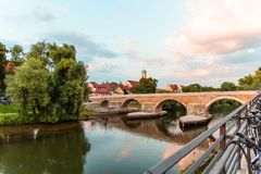 Regensburg, Germany - 26 July, 2018: Footbridge the Stone Bridge across the Danube river. Old monastery and church complex St. Man. G in the background. Popular stock photography