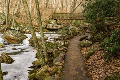 Footbridge, Stone Path, Frozen Creek. A footbridge, stone path by Little Stony Creek located below the Cascade Falls, Jefferson National Forest, Giles County Royalty Free Stock Photos