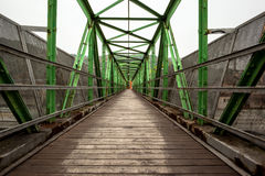 Footbridge with symmetrical metal structure. Narrow long footbridge with symmetrical metal structure Royalty Free Stock Photo