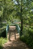 Footbridge to English countryside lake in Summer gardens. Pretty green wooden footbridge to English countryside lake in Summer ornamental gardens Stock Image