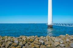 Footbridge towards a wind turbine along a coastline. In spring Royalty Free Stock Image
