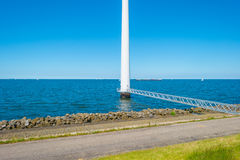 Footbridge towards a wind turbine along a coastline. In spring Royalty Free Stock Images