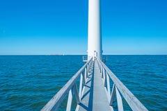 Footbridge towards a wind turbine along a coastline. In spring Stock Photo