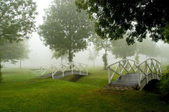 Footbridges. Two identical footbridges in a misty parc. With space for copy stock photography