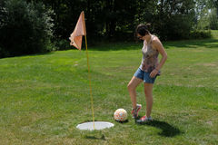 Footgolf Putt. A young lady putting a soccer ball into the footgolf cup Stock Photos