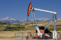 Foothills Oil Well. An oil well pump in the foothills of Alberta with the Rocky Mountains in the background Royalty Free Stock Photography