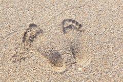 Footmarks på den sandiga stranden Royaltyfria Bilder