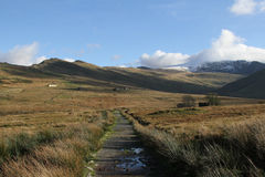 Footpath. Footpath leading into national park land with distant snowy mountains under cloud, abandoned buildings are dotted across the land Stock Photos