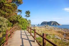 Footpath along the sea on the island of Jeju South Korea beautiful seascape. View of the lighthouse. Travel to Asia stock photos